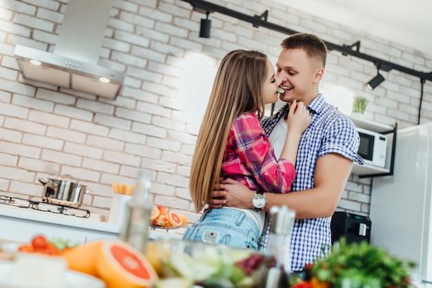 Twee gelukkige mensen spelen met komkommer in moderne witte keuken Premium Foto