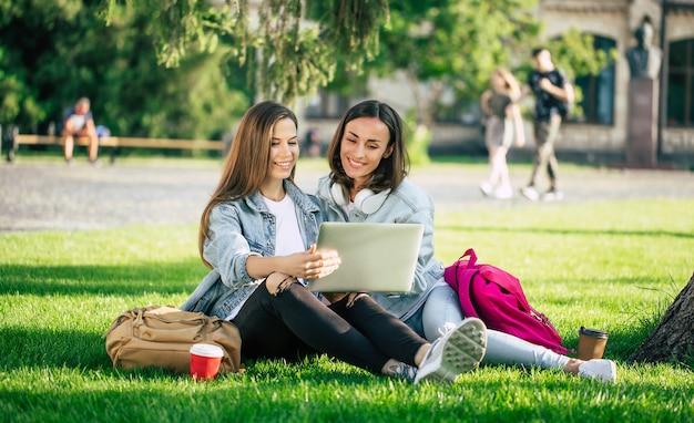 Twee gelukkige mooie jonge student vriendinnen in casual denim kleding zijn ontspannen in college park met laptop en smartphone door de universiteit en koffie drinken.