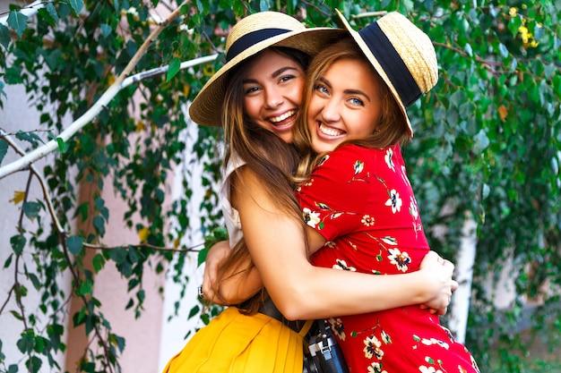 Twee gelukkige mooie jonge zusters, knuffels lachend lachen en grappige gekke tijd samen, met stijlvolle retro vintage vrouwelijke kleding en hoeden. buitenshuis.
