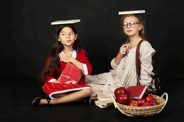 Twee gelukkige mooie vriendinnen schoolmeisjes hebben een leuke zit met boeken