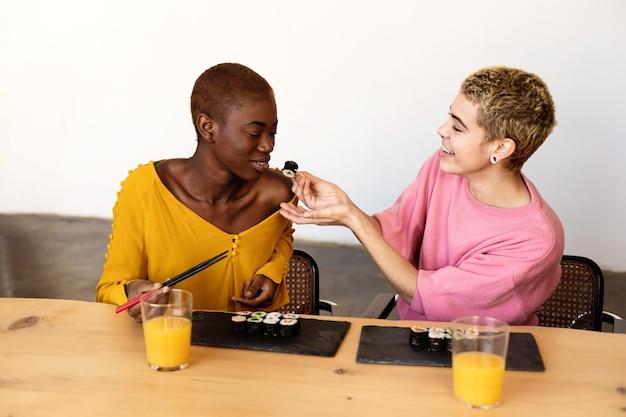 Twee gelukkige mooie vrouwelijke paar vegan sushi rolt eten terwijl om thuis te zitten