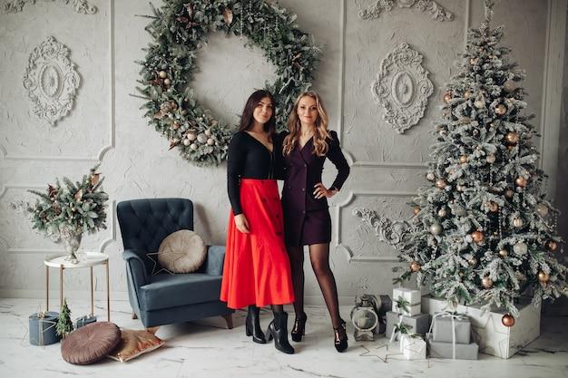 Twee gelukkige mooie vrouwen staan dicht in de kerst versierde kamer