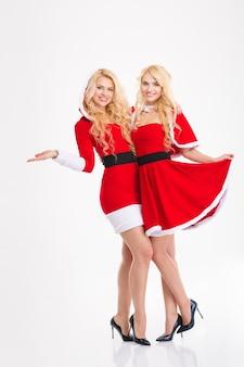 Twee gelukkige mooie zussen tweeling in santa claus kostuums knuffelen en houden copyspace op palm op witte achtergrond