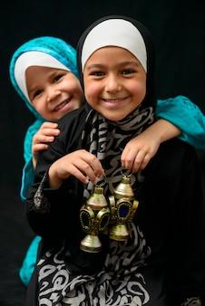 Twee gelukkige moslimmeisjes met ramadan-lantaarn op zwarte achtergrond