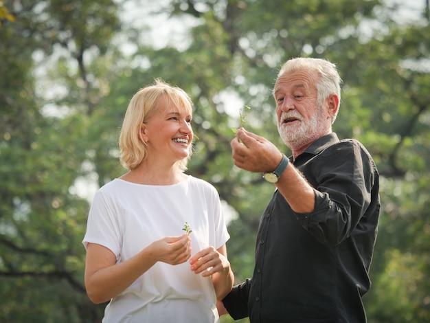 Twee gelukkige oudstenpensionering de man en de vrouw lopen en spreken in park
