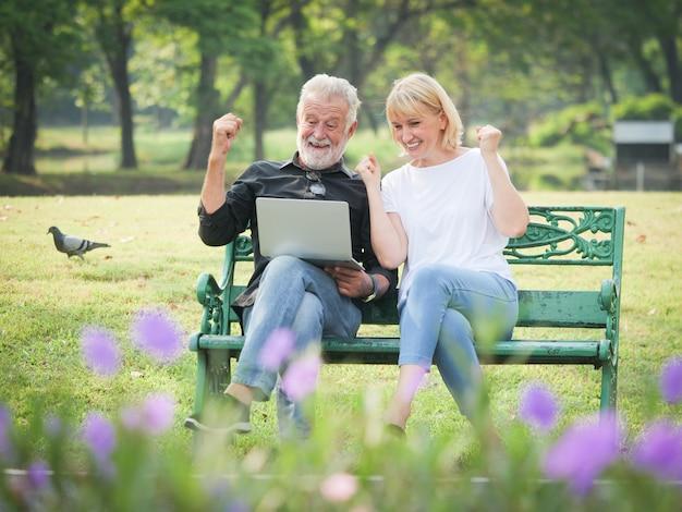 Twee gelukkige oudstenpensionering de man en de vrouw zitten en gebruiken computerlaptop in park
