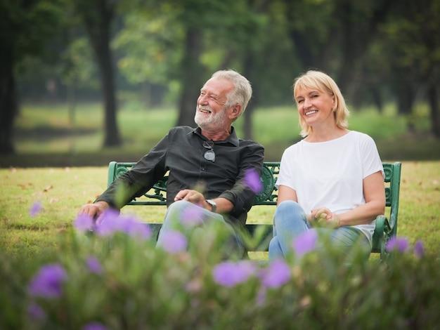 Twee gelukkige oudstenpensionering de man en de vrouw zitten in park en spreken