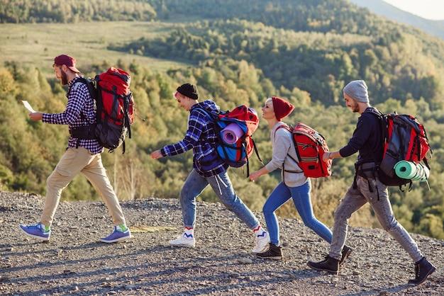 Twee gelukkige paren wandelen in de bergen met de kaart.