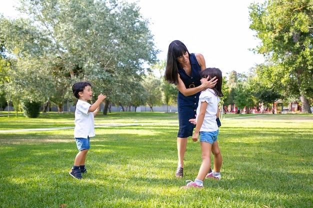 Twee gelukkige schattige kinderen en hun moeder vrije tijd doorbrengen in zomer park, staande op gras, genieten van activiteiten. familie buitenshuis concept