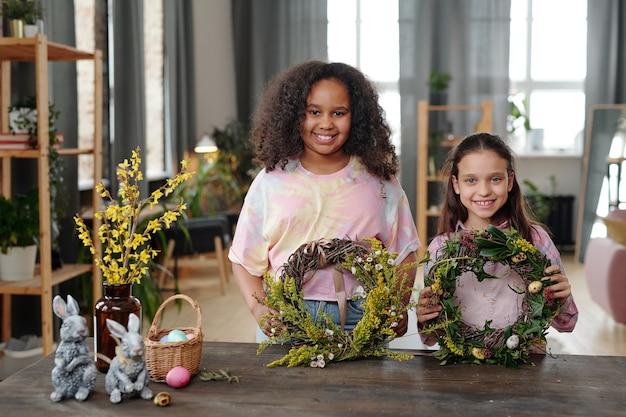 Twee gelukkige schattige kleine meisjes in vrijetijdskleding die naar je kijken met een glimlach terwijl ze bij een houten tafel in een huiselijke omgeving staan en kransen laten zien
