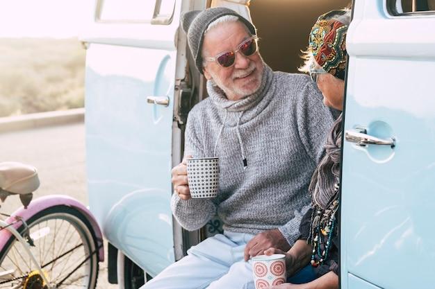 Twee gelukkige senioren en volwassen getrouwd stel die samen de wereld rondreizen met een blauw en wit busje - zittend op het busje met een kopje koffie of thee - bejaarde en gepensioneerde reislevensstijl
