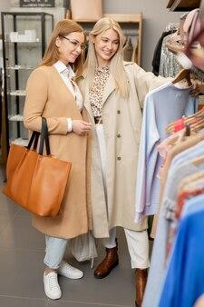 Twee gelukkige stijlvolle eigentijdse vrouwen in elegante jassen staan bij rek in eigentijdse boetiek en kijken door nieuwe collectie