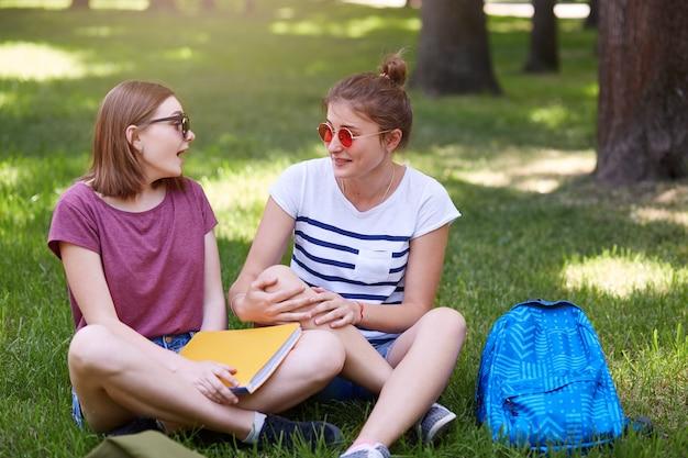 Twee gelukkige studentenvrienden die samen in park met groen gras lachen, zitten in lotushouding, dragen vrijetijdskleding en zonnebril