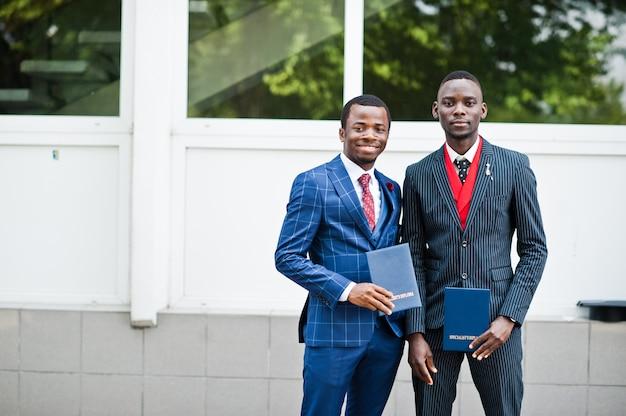 Twee gelukkige succesvolle mannen op pak met diploma op afstuderen dag