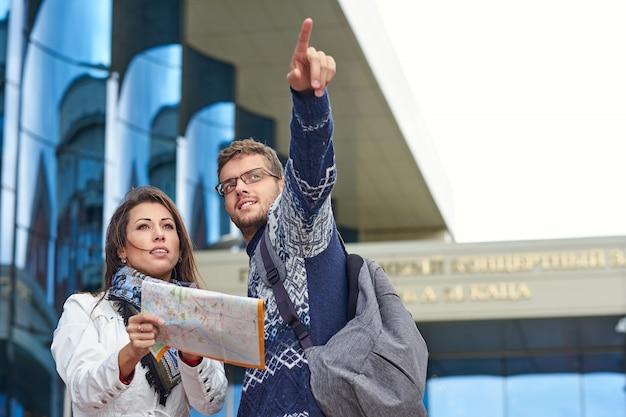 Twee gelukkige toeristen koppelen het zoeken van locatie samen met een telefoon en een kaart en wijzen met de vinger