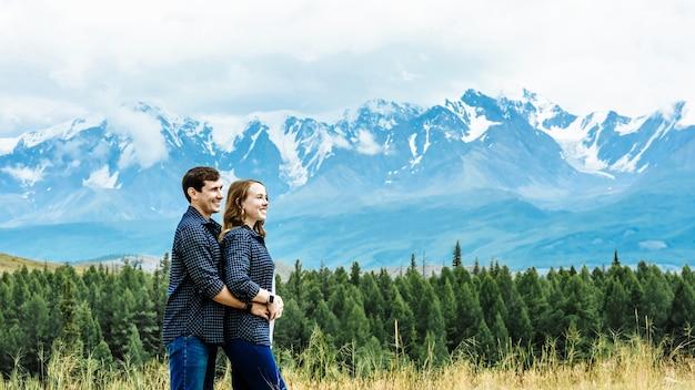 Twee gelukkige toeristen man en vrouw in dezelfde vrijetijdskleding op de achtergrond van de berg op vakantie. jonge glimlachende familie. reis- en reisconcept