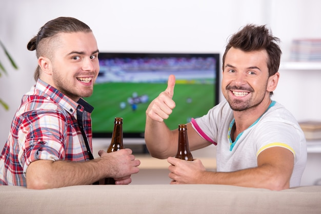Twee gelukkige voetbalfans tijdens het kijken naar favoriete team op tv.