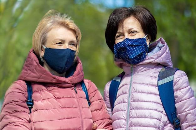 Twee gelukkige volwassen volwassen vrouwen, vrienden in beschermende maskers op gezicht glimlachen, praten, wandelen buiten in de stad, samen plezier. coronavirus, virus, sociale afstand, covid-19 concept.