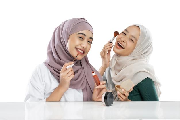 Twee gelukkige, vriendelijke gesluierde meisjesvloggers die een penseel vasthouden en lippenstift aanbrengen