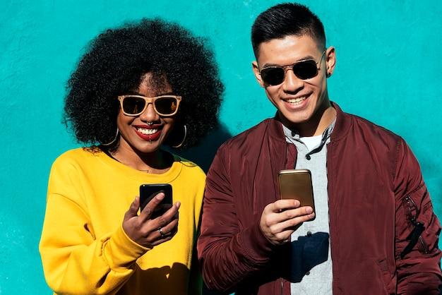 Twee gelukkige vrienden die de mobiel op straat gebruiken. vriendschapsconcept.