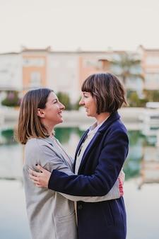 Twee gelukkige vrienden knuffelen op straat
