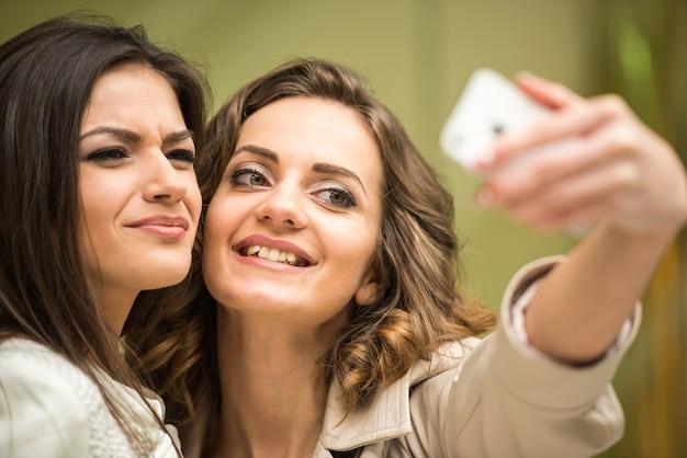 Twee gelukkige vrienden nemen selfie tijdens het winkelen in winkelcentrum.