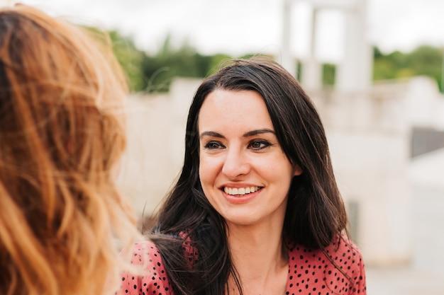 Twee gelukkige vrienden praten en lachen buiten in de open lucht.