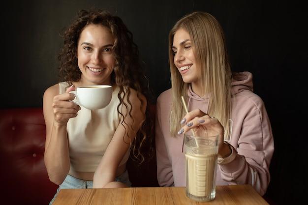 Twee gelukkige vrienden praten tijdens een gesprek in een coffeeshop