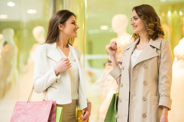 Twee gelukkige vrienden winkelen in wandelgalerij.