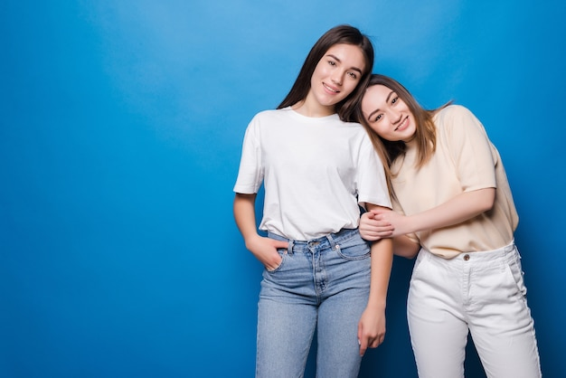 Twee gelukkige vriendinnen geïsoleerd op blauwe muur