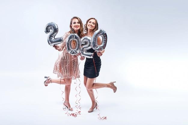 Twee gelukkige vriendinnen met metalen 2020-ballonnen op wit.