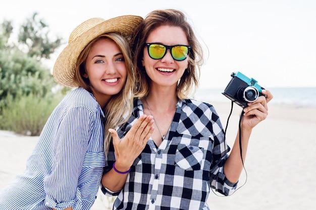 Twee gelukkige vriendinnen met plezier op het strand