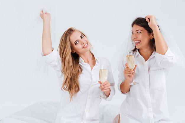 Twee gelukkige vrolijke meisjes die een pre-huwelijksfeest hebben met glazen champagne