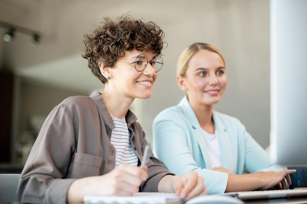 Twee gelukkige vrouwelijke collega's kijken naar gegevens op het computerscherm tijdens de bespreking van nieuwe ideeën voor project