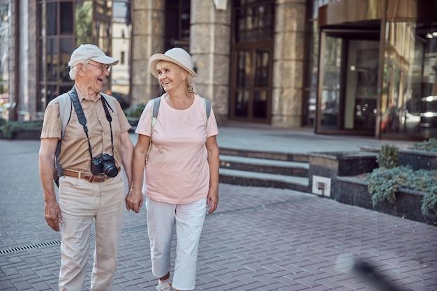Twee gelukkige vrouwelijke gepensioneerden die hand in hand door het stadscentrum wandelen