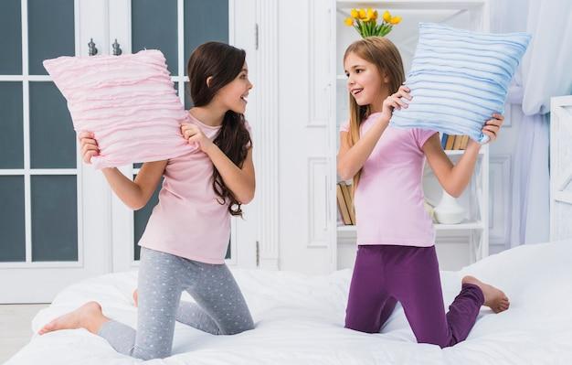Twee gelukkige vrouwelijke vrienden die hoofdkussenstrijd op bed thuis doen
