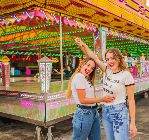 Twee gelukkige vrouwelijke vrienden die hun wapens opheffen bij pretpark