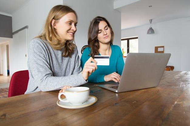 Twee gelukkige vrouwelijke vrienden die laptop met behulp van