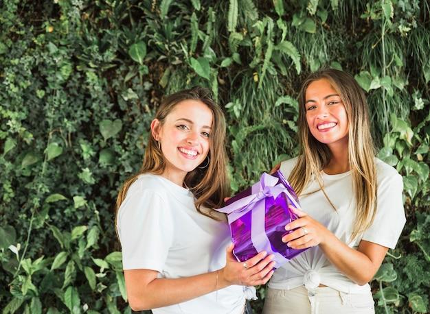 Twee gelukkige vrouwelijke vrienden die purpere giftdoos houden