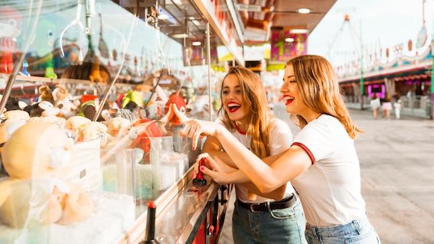 Twee gelukkige vrouwelijke vrienden die stuk speelgoed het grijpen spel spelen bij pretpark