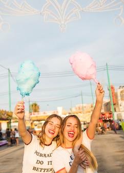 Twee gelukkige vrouwelijke vrienden met suikerspin die hun wapens opheffen