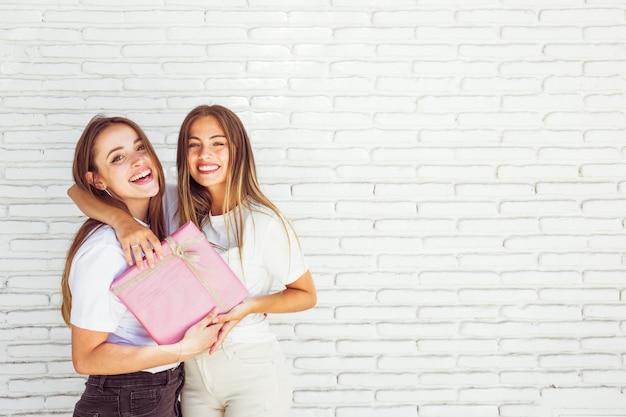 Twee gelukkige vrouwelijke vrienden met verjaardagsgift voor bakstenen muur