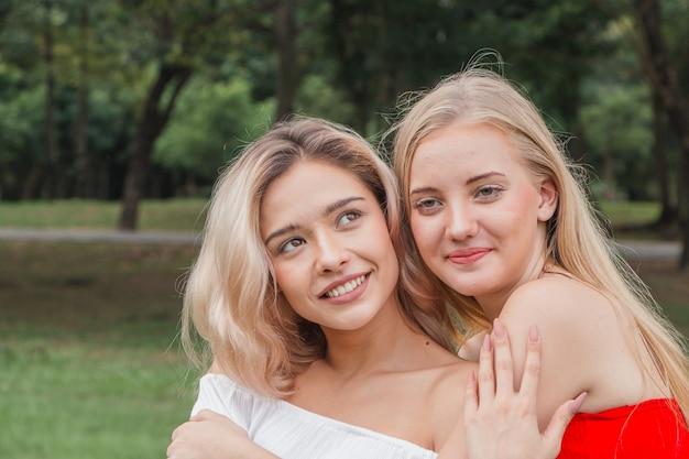 Twee gelukkige vrouwen buiten knuffelen en glimlachen