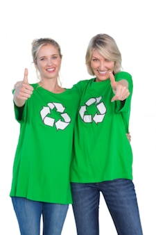 Twee gelukkige vrouwen die groene recyclingst-shirts dragen die duimen opgeven