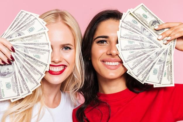 Twee gelukkige vrouwen die hun halve gezichten behandelen en de camera over roze bekijken