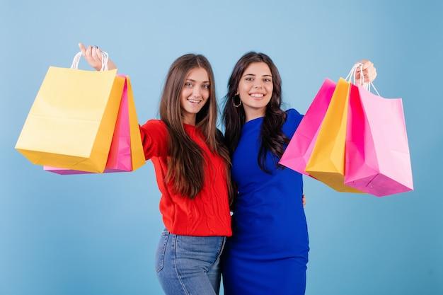Twee gelukkige vrouwen die kleurrijke die het winkelen zakken houden over roze worden geïsoleerd