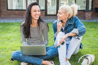 Twee gelukkige vrouwen die op gras met laptop zitten