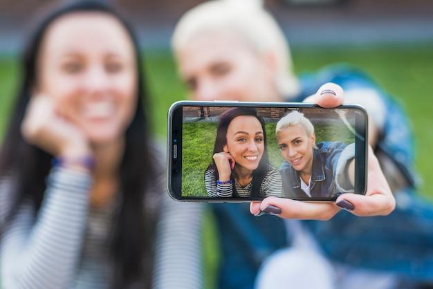 Twee gelukkige vrouwen die selfie op mobiele telefoon nemen