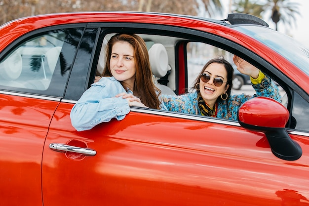 Twee gelukkige vrouwen die uit van autoraam kijken