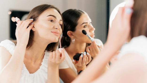 Twee gelukkige vrouwen dragen make-up en kijken in een spiegel in een schoonheidssalon